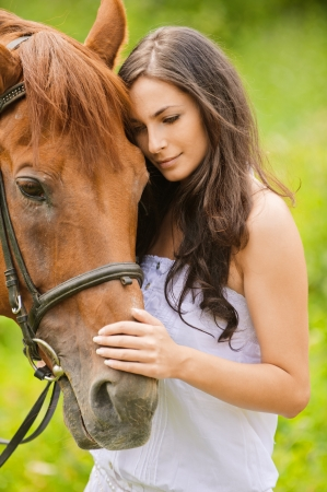 fondling: Portrait of young beautiful woman with brown horse at summer green park.