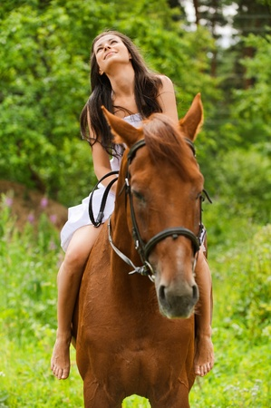 buoyant: Portrait of young smiling brunette woman, looking to sky, wearing white dress and riding horse at summer green park.