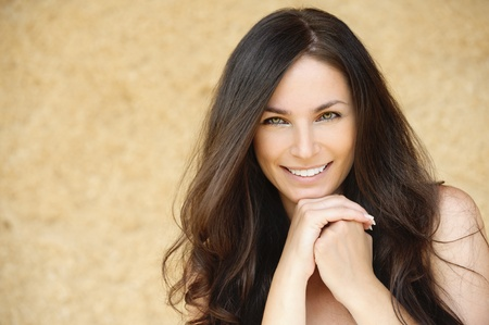 model nice: Portrait of young charming cheerful woman propping up her face against beige background.
