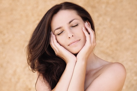 meditative: Portrait of young beautiful woman with eyes closed propping up her face against beige background.