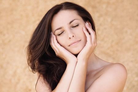 ojos cerrados: Retrato de joven bella mujer con los ojos cerrados apuntalar su cara contra el fondo beige.