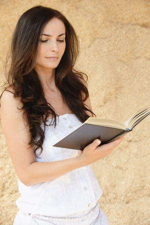 ravishing: Young attarctive woman reading book against beige background. Stock Photo