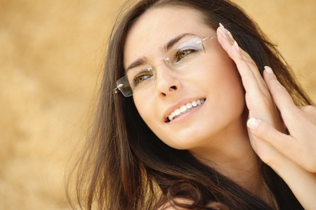 witty: Close-up portrait of young alluring woman wearing eyeglasses against beige background.