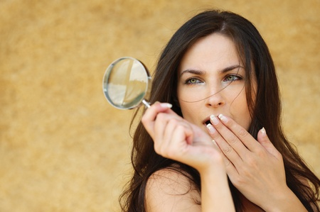 naturalist: Portrait of young attractive amazed woman holding loupe and covering her mouth with hand against yellow background.