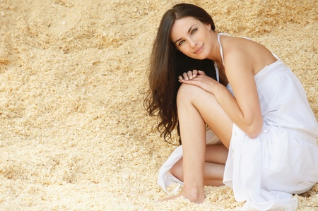 belles jambes: Portrait de jeune femme brune charmante porter robe blanche assis dans la sciure.