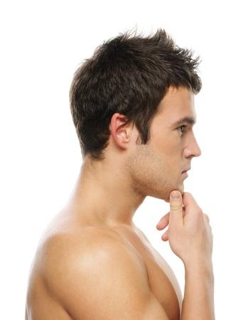 hombre de perfil: Retrato de hombre joven reflexivo contra el fondo blanco. Foto de archivo