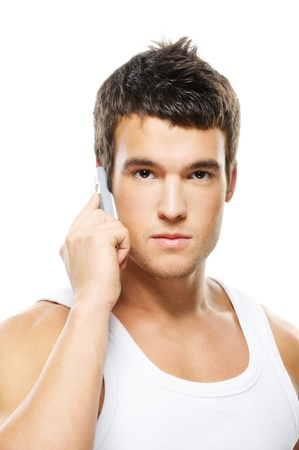likable: Portrait of young handsome brunette man speaking on mobile phone against white background. Stock Photo
