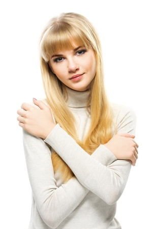innocent girl: Portrait of young alluring blonde woman wearing jersey, embracing herself against white background.