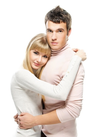 russian man: Two young people: smiling blonde woman and serious dark-haired man embracing against white background.