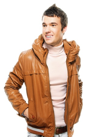 engaging: Portrait of young smiling brunette man wearing brown leather jacket against white background.