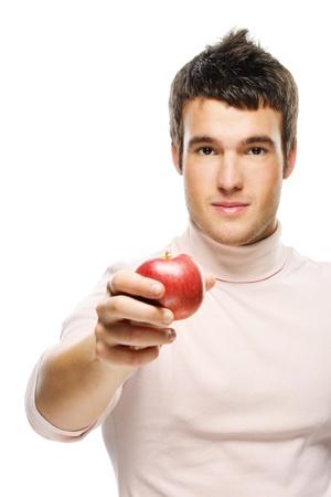 generoso: Retrato de joven guapo hombre de pelo oscuro llevando jersey beige, sosteniendo la manzana roja sobre fondo blanco.