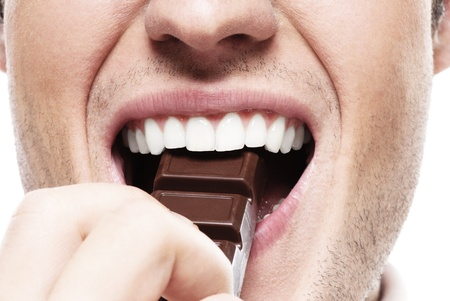 tastes: Mouth of man eating chocolate against white background. Stock Photo