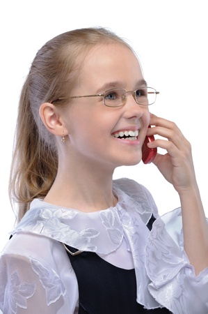 Portrait of little fair-haired laughing girl speaking on mobile phone against white background. photo