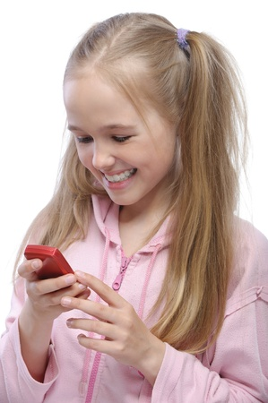 Portrait of little fair-haired girl wearing pink jacket, smiling and looking at mobile phone against white background. photo