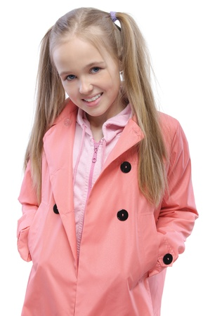 raincoat: Portrait of little fair-haired smiling girl wearing pink raincoat, standing against white background. Stock Photo