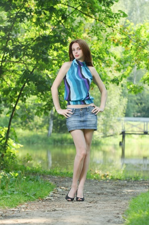 teen legs: Full-length portrait of young pretty woman wearing blue blouse, jean skirt and black shoes standing at summer green park. Stock Photo