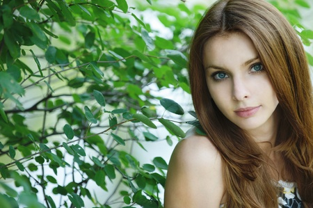 Portrait of young attractive woman at summer green park. photo
