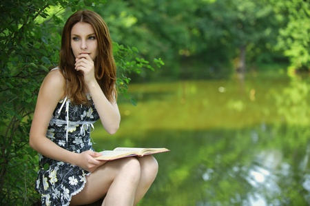 Portrait of young pensive girl holding book, wearing black dress at summer green park. photo