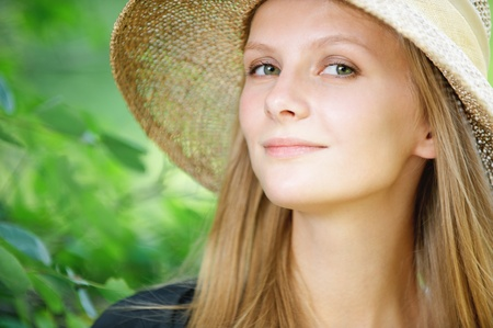 artful: Close-up portrait of young beautiful blonde woman wearing straw hat at summer green park. Stock Photo