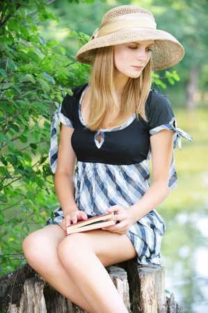 Portrait of young beautiful fair-haired woman holding book, wearing straw hat and dress, sitting on stump against lake at summer green park.