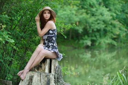 Portrait of young beautiful woman wearing straw hat and black dress, sitting on stump against lake at summer green park. photo