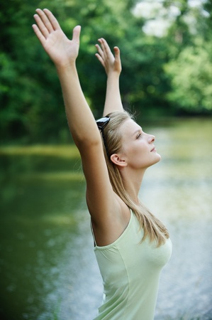 Portrait of young pretty woman holding hands up against lake at summer green park. Stock Photo