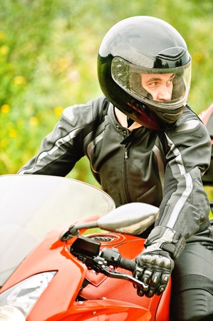 Portrait of young man wearing helmet, leather costume, driving red motorbike. photo