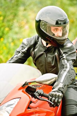 motociclista: Retrato de joven llevaba casco, traje de cuero, conducir moto roja. Foto de archivo