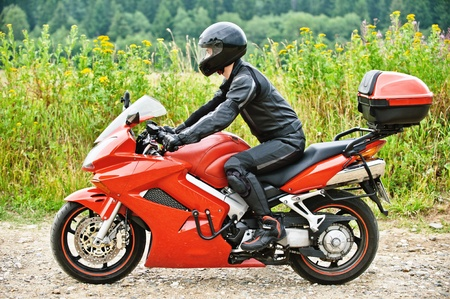 Motorcyclist driving red motorbike, wearing leather costume and helmet against peaceful scenery. photo