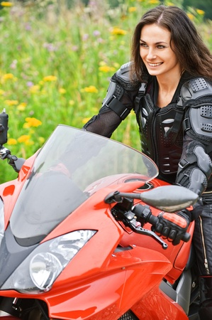 Portrait of young attractive dark-haired smiling woman wearing protective costume, driving red motorbike. Stock Photo