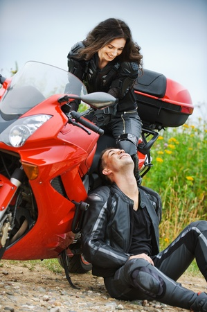 motorcyclist: Two people: young beautiful woman sitting on motorbike and smiling man having rest.