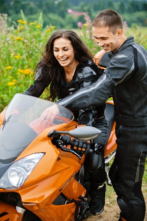 Two laughing young people: pretty brunette lady sitting on motorbike and handsome dark-haired man standing near. photo