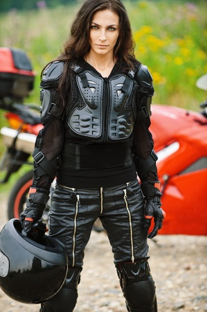 motorcyclist: Portrait of young severe brunette woman wearing protective costume and holding helmet. standing against red motorbike.