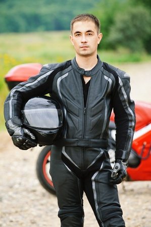 Portrait of young serious dark-haired man wearing black leather costume and holding helmet against red motorbike. photo