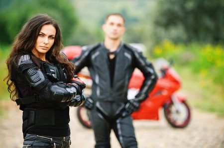 Two young people: pretty brunette woman and handsome man standing against red motorbike. photo