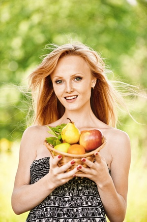 generous: Portrait of young pretty blonde smiling woman wearing black top, holding basket with fruits at summer green park.