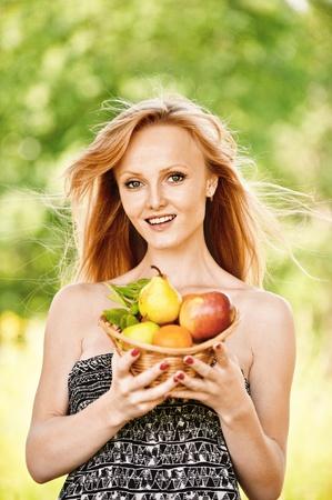 generoso: Retrato de joven rubia bastante sonriente mujer llevando top negro, sosteniendo la cesta con frutas en el Parque de verano verde. Foto de archivo