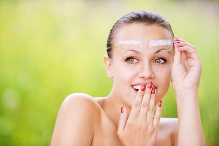 ridicolo: Ritratto di giovane donna bella bruna con gli occhiali, guardando qualcosa di ridicolo e copre la bocca con la mano in estate parco verde.