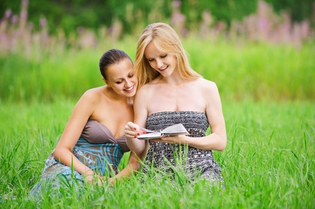 Two young beautiful smiling women reading book, sitting on grass at summer green park. photo