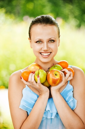 buoyant: Portrait of young beautiful dark-haired woman wearing blue blouse, holding a lot of fruits at summer green park.