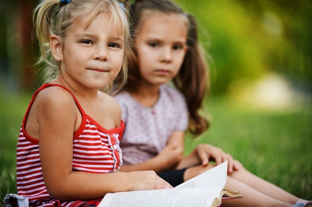 clever: Two little pretty girls reading book at summer green park.