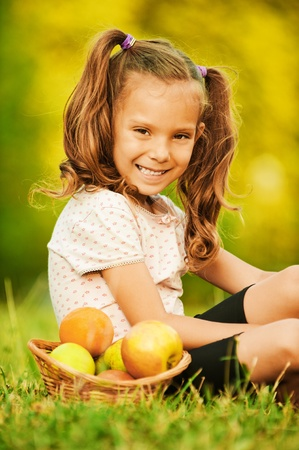 Portrait of pretty little girl wearing white t-shirt and black shorts, sitting near basket full of fruits on grass at summer green park. photo