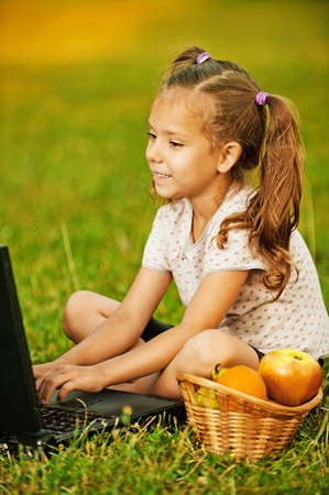 Portrait of little smiling pretty girl wearing t-shirt and shorts working with laptop at summer green park. Stock Photo - 10407241