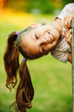 weekends: Portrait of little pretty laughing girl playing at summer green park. Stock Photo