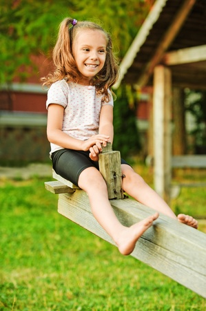Portrait of little smiling girl wearing white t-shirt and shorts having fun on seesaw at summer green park. photo