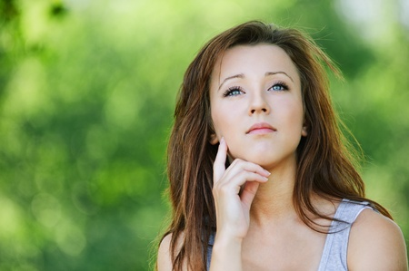 Portrait of pretty dark-haired pensive girl at summer green park. photo