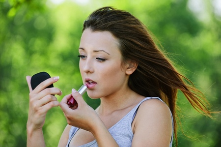 ravishing: Portrait of pretty dark-haired teenage girl colouring her lips with lipstick and looking in mirror at summer green park.