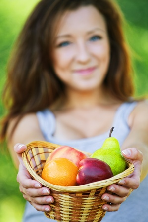 Portrait of pretty young smiling woman wearing grey t-shirt and holding basket full of ripe fruits at summer green park. photo