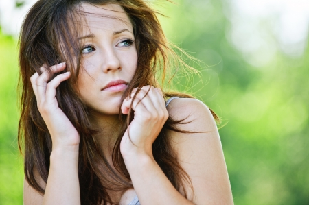 Portrait of troubled beautiful brunette girl looking somewhere at summer green park. Stock Photo - 10422290