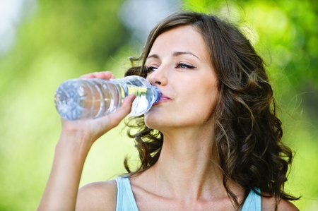 bottle with water: Portrait of young beautiful dark-haired woman wearing blue t-shirt drinking water at summer green park.